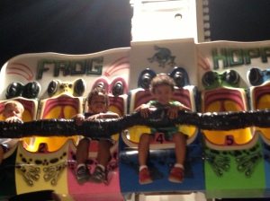"Fuzzy picture but oh well. The boys rode an insane number of roller-coasters, ponies, trains, and other thrill rides this summer. It's gotten to the point that they are bored with the standard kiddie rides. This is what you get when a carney tells you it's okay for your 4 year old to ride a 90 foot high drop tower and you agree. Kelly and I should be writing a book called ""How to Raise a Thrill Junkie""."